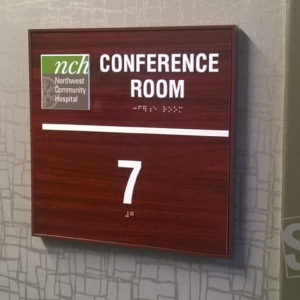 conference room sign with raised logo and copy and grade II braille rastors